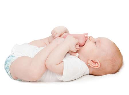 乳幼児: かわいい女の赤ちゃん白い背景の上に彼女のつま先をしゃぶり