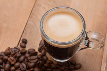 field glass: Glass Cup of Espresso Coffee on Wooden Table With Coffee Beans With Copyspace - Shallow Depth of Field