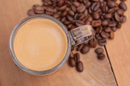 expresso: Top View of Glass Cup of Espresso Coffee on Wooden Table With Coffee Beans - Shallow Depth of Field