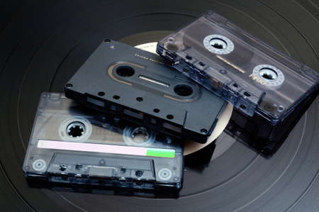 80 s: Photo of Retro Audio Cassette Tapes - Long Play Vinyl Record in Background Stock Photo
