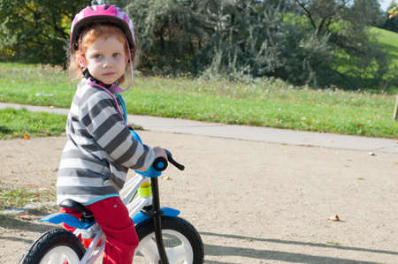 Child girl with the safety helmet on the bike in the autumn park photo
