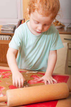 Little girl baking cutting pastry for Christmas cookies photo