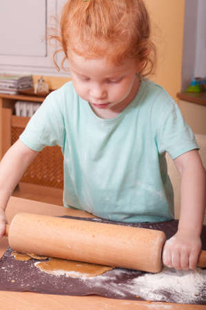 Little girl baking rolling pastry for Christmas cookies photo