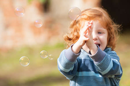 Happy girl trying to catch soap bubble Stock Photo