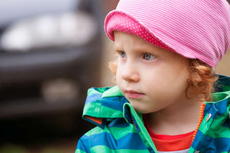 Portrait of thoughtful little girl with car in background photo