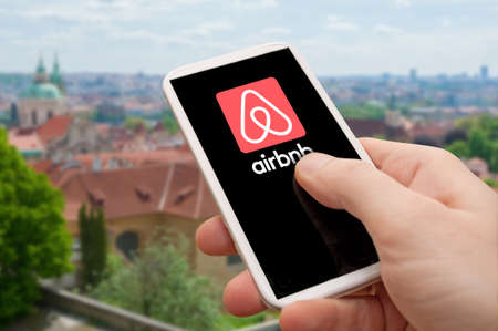 PRAGUE, CZECH REPUBLIC - JUNE 25, 2017: Photo of hand holding phone with Airbnb logo on the screen. Prague city in background