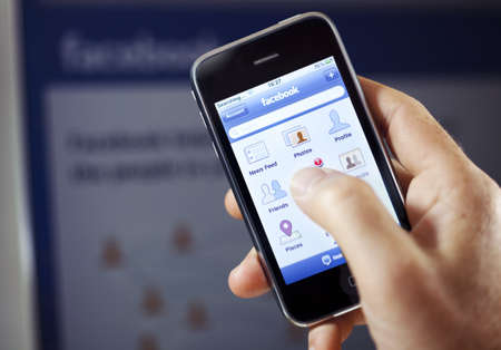 Aachen, Germany - August 01, 2011: Close up of an Apple iPhone 3GS screen showing the Facebook App Page, while an open Facebook Page is out of focus on a LCD screen in the background.