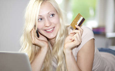Smiling young woman using laptop, holding golden credit card photo