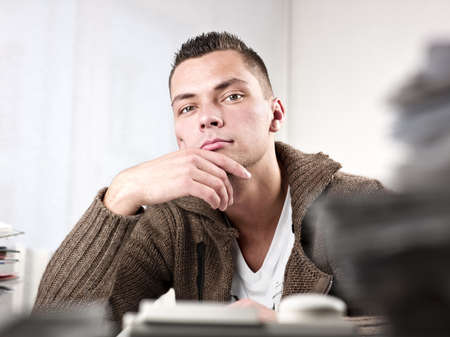 Young handsome businessman thinking at office. Horizontal shot Stock Photo