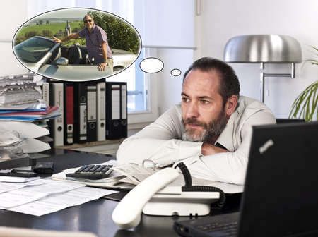 Mature businessman at desk with a thought bubble of himself and new car countryside. Horizontal shot photo