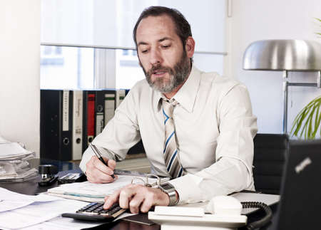 busy beard: Mature businessman calculating finance. Horizontal shot Stock Photo