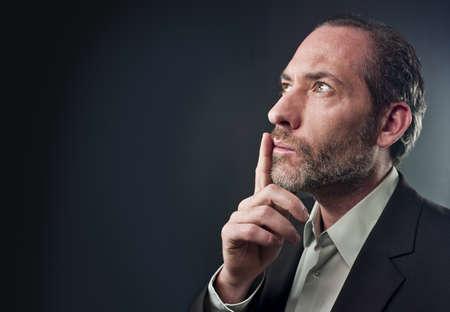 side profile: Studio shot di affari in una profonda riflessione su uno sfondo colorato (girato in PhaseOne 45)