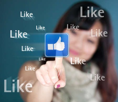 Cute young woman is touching the like button photo