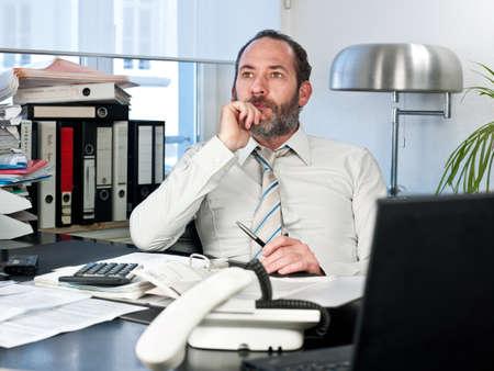Contemplative businessman looking away at work  Horizontal shot photo