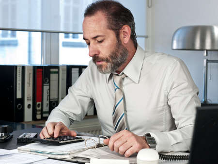 Mature businessman calculating finance  Horizontal shot photo