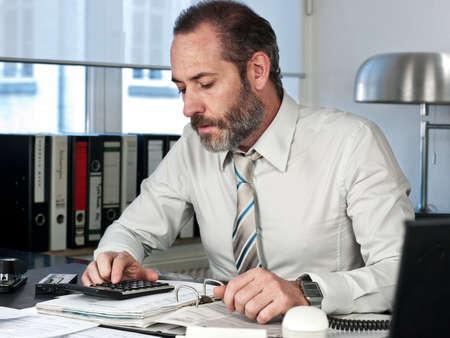 busy beard: Mature businessman calculating finance  Horizontal shot