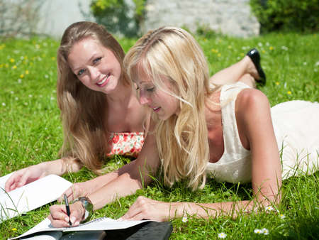 cute girlfriends: two girls are learning outside in the park