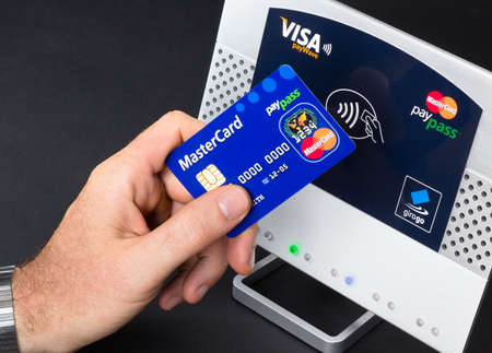 Aachen, Germany - August 05, 2012: Studioshot of payment action with the mastercard paypass credit card in front of a NFC terminal wich accepts visa, mastercard, american express and girogo contactless payments.