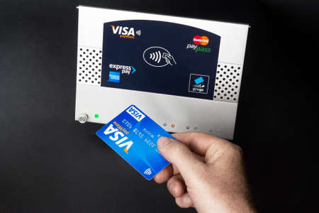 accepts: Aachen, Germany - August 05, 2012: Studioshot of payment action with the Visa paywave credit card in front of a NFC terminal wich accepts visa, mastercard, american express and girogo contactless payments. Editorial