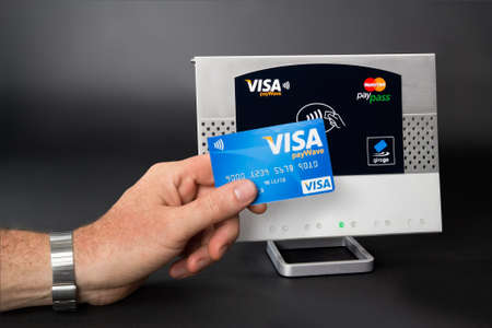 Aachen, Germany - August 05, 2012: Studioshot of payment action with the Visa Paywave credit card in front of a NFC terminal wich accepts visa, mastercard, american express and girogo contactless payments. Editorial