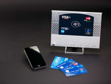 accepts: Aachen, Germany - August 05, 2012 - Studioshot of payment variations ( Apple iPhone 4, Visa paywve, mastercard paypass) in front of a NFC terminal wich accepts visa, mastercard, american express and girogo contactless payments. Editorial