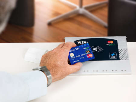 accepts: Aachen, Germany - August 11, 2012- Studioshot of payment action with the mastercard paypass credit card in front of a NFC terminal wich accepts visa, mastercard, american express and girogo contactless payments. Editorial