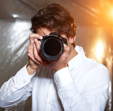 studio photography: Young handsome photographer on the hunt Stock Photo