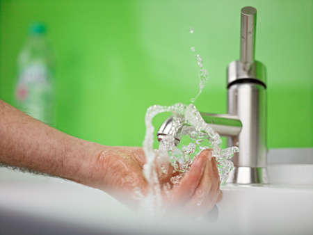 holding hand under sparkling fresh water out of the faucet Stock Photo - 17340314