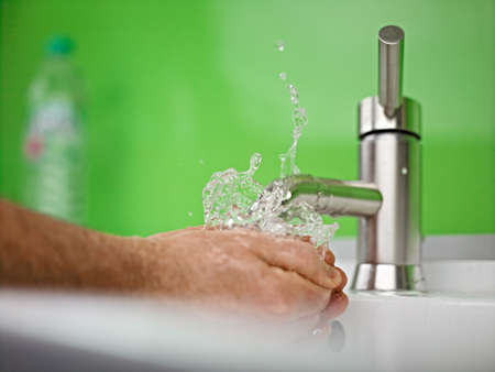 holding hand under sparkling fresh water out of the faucet Stock Photo - 17340312