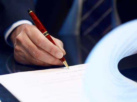 signing authority: Businessman sitting at shiny office desk signing a contract with noble classic pen
