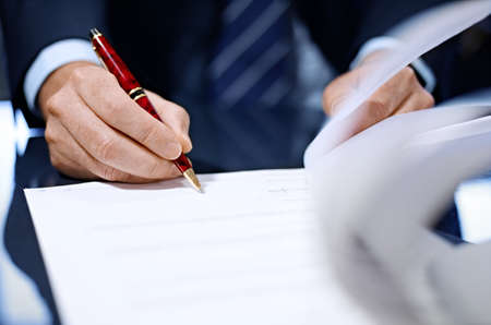 signing authority: Businessman sitting at shiny office desk signing a contract with noble pen