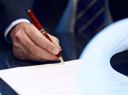Businessman sitting at shiny office desk signing a contract with noble classic pen
