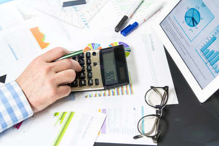 Businessman uses his calculator to get the final company results photo