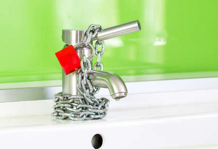 drippings: a waterdrop is dripping out of a modern faucet, locked by a red lock and chain Stock Photo