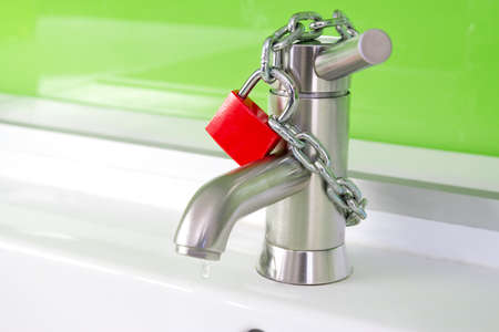 clean water: a waterdrop is dripping out of a modern faucet, locked by a red lock and chain Stock Photo