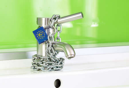 a waterdrop is dripping out of a modern faucet, locked by a lock and chain from the european commission Stock Photo - 18428423