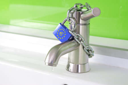 a waterdrop is dripping out of a modern faucet, locked by a lock and chain from the european commission