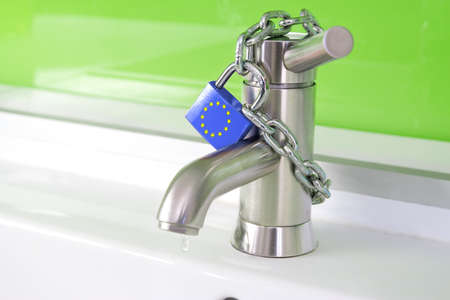 a waterdrop is dripping out of a modern faucet, locked by a lock and chain from the european commission photo