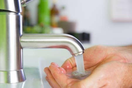 tenendo la mano sotto acqua fresca frizzante dal rubinetto Archivio Fotografico