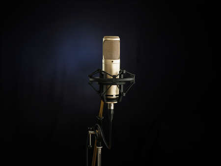 vocals: golden broadcast voice microphone on dark background Stock Photo