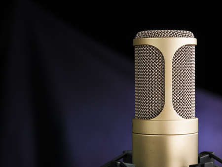 golden broadcast voice microphone on dark background - closeup shot photo