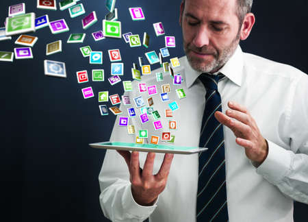 a mature businessman or salesman shows his pad with lots of apps flying around