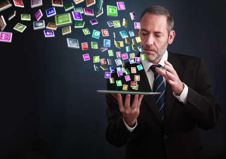 成熟したビジネスマンやセールスマン彼のパッドの周りを飛んでのアプリの多くを示しています 写真素材