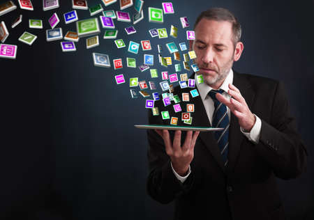 a mature businessman or salesman shows his pad with lots of apps flying around photo