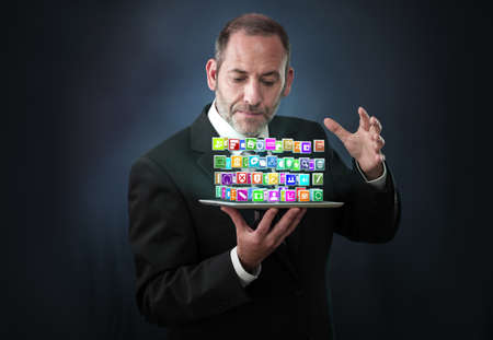 a mature businessman wizard conjures a lots of apps flying around his pad or tablet PC