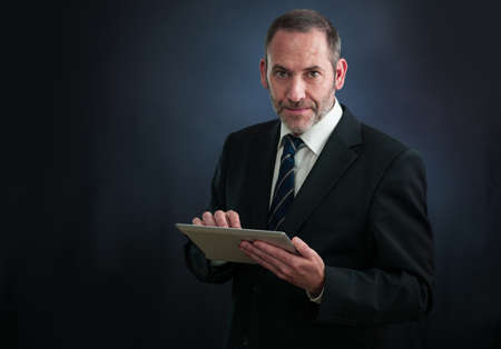 Happy Mature businessman working with tablet PC , smiling into the camera photo