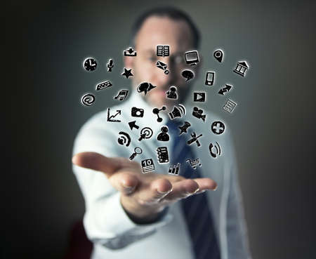a mature businessman or salesman shows his hand with lots of apps flying arround Stock Photo