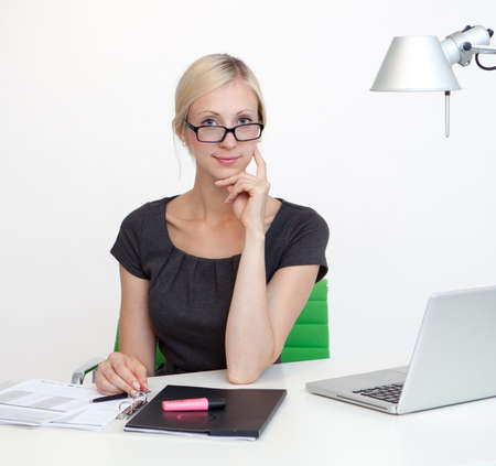 Young Business woman is smiling while working at work desk Stock Photo - 26712113