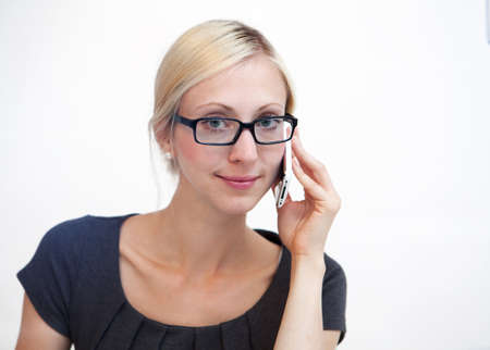 Happy blond businesswoman talking on phone against white background photo