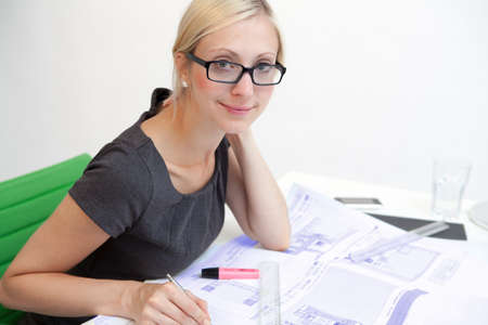 outwork: Business woman with blueprint at workplace Stock Photo